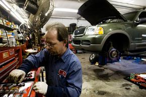 Al Van Sant, a mechanic at East Falls Gulf Service Station, gathers tools for brake work on an SUV in Philadelphia.