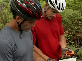 Two mountain bikers find their way with a GPS unit.