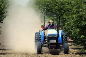 A worker tills the soil on a farm near Hanford, Calif.