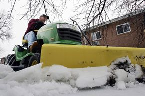 Steve Daurizio plows snow with a tractor in Morrisville, Pa.