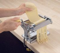 Using the desired attachment, feed the                    dough through the pasta machine.