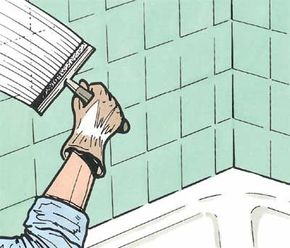 Spread grout evenly over the wall using a rubber squeegee to work the grout into the areas between the tiles.