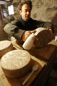 The author Brad Kessler checks his homemade goat cheese in Vermont.