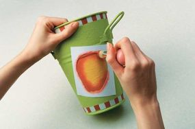 Spray adhesive adheres the apple stencil to the bucket.