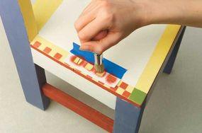 To make the border, tape the checkerboard stencil to the edge.