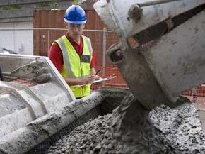 A construction worker pours some concrete from a rotating drum mixer.