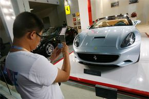 A man takes photos of a Ferrari California at an auto exhibition in Beijing, China, in 2009. The five-day exhibition showcased imported cars, many of them high-priced luxury models.