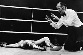 A boxing referee administers the count.