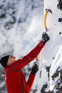 A Colorado ice climber plants his ice tool in the ice.
