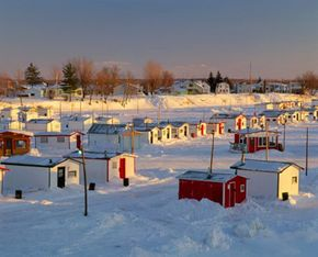 Ice shelters dot Sainte-Anne-de-la-Perade River in Mauricie County, Quebec.