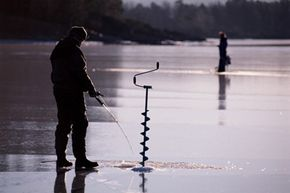 A man in Norway uses an auger to bore a hole in the ice.
