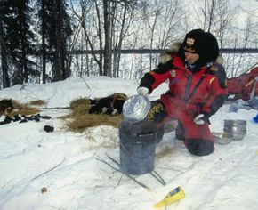 Musher Jeff King prepares meals for his sled dogs during the Iditarod Trail Race in Eagle Island, Alaska.