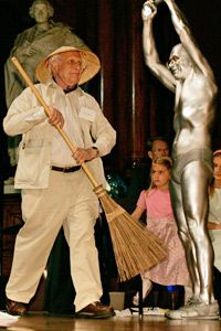 Physicist and Nobel Prize laureate Roy Glauber sweeps up paper airplanes during the 2006 Ig Nobel awards. The annual awards poke fun at bizarre achievements in scientific research.