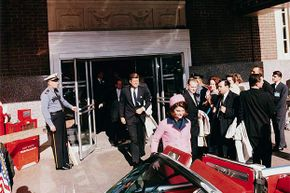 President John F. Kennedy and First Lady Jacqueline Kennedy emerge from a Fort Worth, Texas theater into a waiting car  on the day of his assassination.