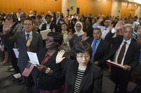 People take the U.S. citizenship oath during a naturalization ceremony at the U.S. Patent and Trademark Office in Alexandria, Virginia, May 28, 2015.