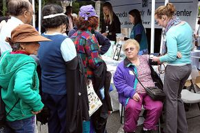 A senior citizen receives a free blood pressure check during a healthy living festival in Oakland, California. Common thinking is that most immigrants come to the U.S. for the benefits but studies show they use less of them than native-borns.
