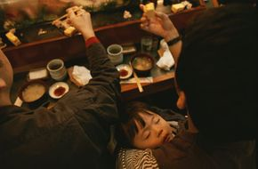 A man holds his baby while eating in a sushi restaurant in Tokyo, Japan. See more sleep pictures.