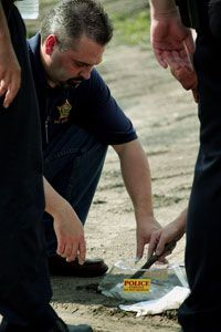 Hammond, Ind. police officers make a mold of a tire track near the scene of a reported sniper shooting.