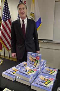 FBI Director Robert Mueller shows off pirated copies of Windows 98 seized in Operation Cyberstorm.