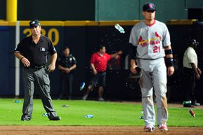 Umpire Rob Drake reacts after bottles are thrown on the field by Atlanta fans angry at an infield fly ruling on a ball hit by an Atlanta Braves player while taking on the St. Louis Cardinals during a wild card playoff game in 2012. See more baseball pictures.