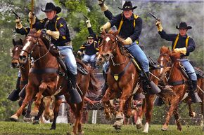 Gunpowder and dirt hang in the air as the U.S. Army's 1st Cavalry Division horse detachment make their traditional 'cavalry charge' to conclude a March 25, 2009, ceremony at Fort Hood, Texas.