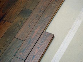 Laminate flooring is cheaper than wood, doesn't need to be nailed, sanded, stained or finished, and is quite resistant to scratches, denting, fading and stains.