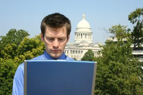 Guy looking at laptop with Capitol in background