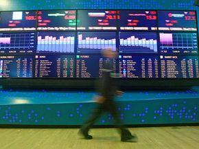 A trader walks past monitors at the New York Stock Exchange on March 30, 2009. The Dow dropped 288 points that day on news that Chrysler and General Motors may declare bankruptcy.