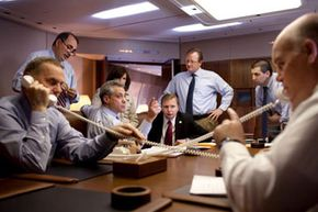 The Obama presidential staff manages multiple calls during a meeting.