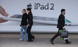 A shopper who had just bought the new Apple iPad 2 on the first day the tablet computer went on sale walks past an advertisement for the device in Berlin, Germany.