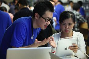 Apple staff introduce iPad tablets to customers at the Apple store on Sept. 17, 2010 in Beijing, China. See more banking pictures.