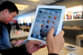A customer experiences an iPad 2 at the Sanlitun Apple Store in Beijing, China.