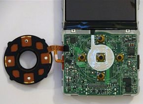 Behind the Click Wheel face (left) and Click Wheel contacts on the motherboard