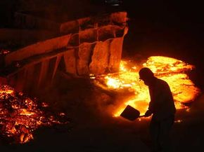 A worker covers the steel slag poured on the ground with sandy soil at a stainless steel factory.