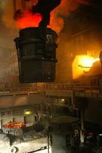 A ladle filled with molten iron approaches a blast furnace that will convert it to liquid steel.