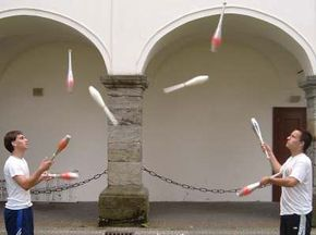 Two jugglers practice passing.