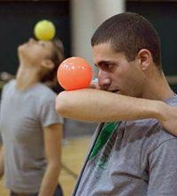 Two jugglers practice contact juggling.