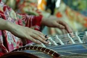 A woman plays the koto, the national instrument of Japan, which is a whopping six feet long (1.83 meteres) and has 13 strings.