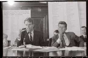 """Robert Kennedy (left) questions James R. (""""Jimmy"""") Hoffa during a hearing of the Senate Labor Rackets Committee in 1957 while then-Sen. John Kennedy looks on."""