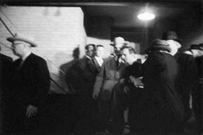 Jack Ruby shoots Lee Harvey Oswald as he is escorted from Dallas police headquarters.
