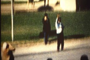 """The film """"JFK"""" posited that the men with the umbrella and the radio are giving the signal to Kennedy's shooter(s).  In 1978, a man came forward claiming to be """"Umbrella Man"""" and said he only used the umbrella to heckle Kennedy."""