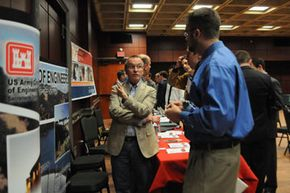 At a college job fair, a student discusses job opportunities with civil engineer Roger Henderson of the U.S. Army Corps of Engineers.
