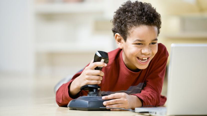 Boy playing game with a joystick on laptop