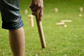 A player prepares to throw a baton in a game of kubb.