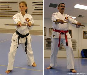 At Karate International of Raleigh, advanced karatekas may take up a traditional martial arts weapon. On the right, Rob Olevsky holds the Nunchaku. On the left, Mindy Mayernik wields the long staff.