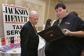Many Americans have not saved enough for retirement. Here, an agent with Jackson Hewitt Tax Service talks with 78-year-old job-seeker Louis Brown as they peruse information on a laptop computer at a senior job fair.