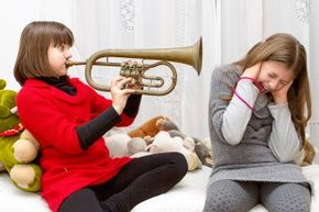 Worst case scenario, your sister's trumpet playing will just make you feel like your head's about to explode. It would take exposure to a far larger instrument for far longer to actually get that explosion.