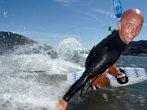 Extreme Sports Image Gallery A kitesurfer skims his hand across the water and flashes the camera a smile. See more pictures of extreme sports.