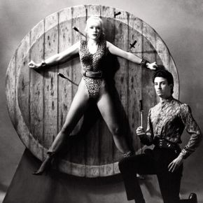 A carnival knife thrower and his comely assistant pose by the wheel of death.