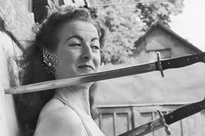 Circus knife-thrower's assistant Honey Del Rio awaits her partner's next throw, circa 1955.